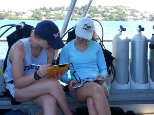 Lucy Webb,`16 and Caroline Booth,`16 review the identification book before reaching the dive site.